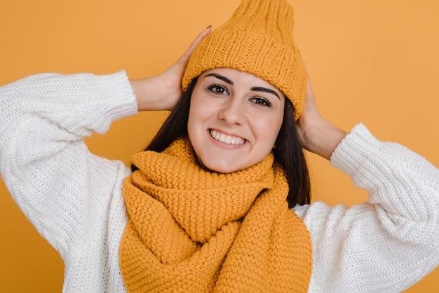 Feche o retrato de uma bela morena de chapéu laranja, sorri sinceramente