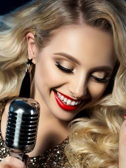 Feche o retrato de uma cantora loira e bonita segurando um microfone de estilo retrô