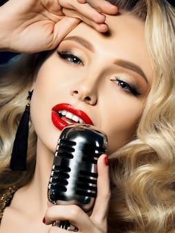 Feche o retrato de uma cantora loira e bonita segurando um microfone de estilo retrô Foto Premium