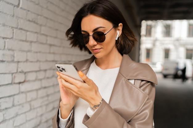 Feche o retrato de uma elegante mulher de cabelo curto com fones de ouvido, um casaco de couro casual e óculos de sol usando o smartphone e posando sobre uma parede de tijolo urbana