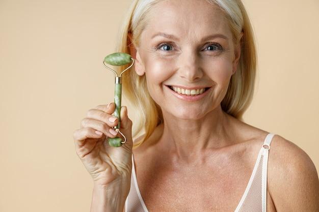 Feche o retrato de uma encantadora mulher loira madura com a pele perfeita, sorrindo para a câmera segurando jade