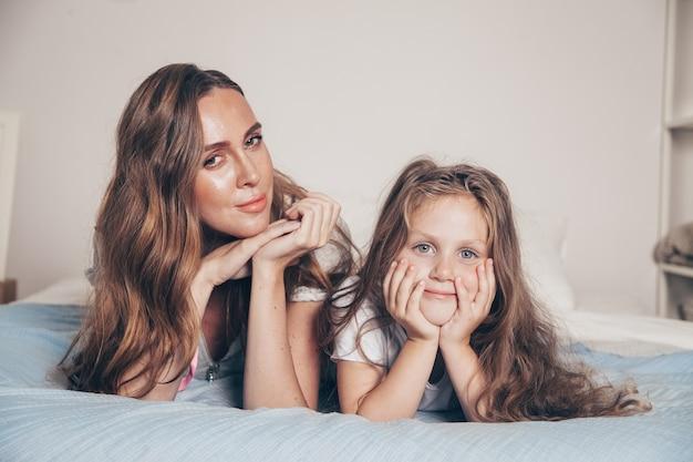 Feche o retrato de uma família amorosa feliz deitada relaxando desfrutando no quarto juntos. mãe e sua filha criança pré-escolar linda garota de pijama deitada na cama.