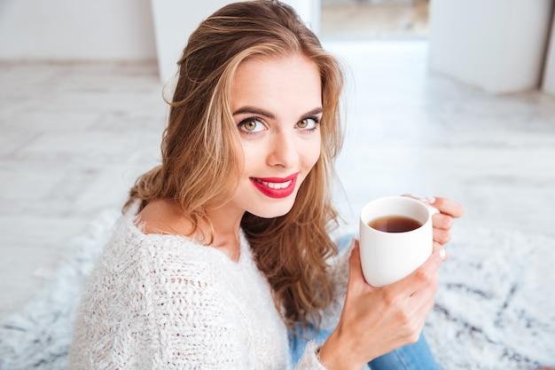 Feche o retrato de uma garota atraente sorridente com suéter segurando uma xícara de chá dentro de casa