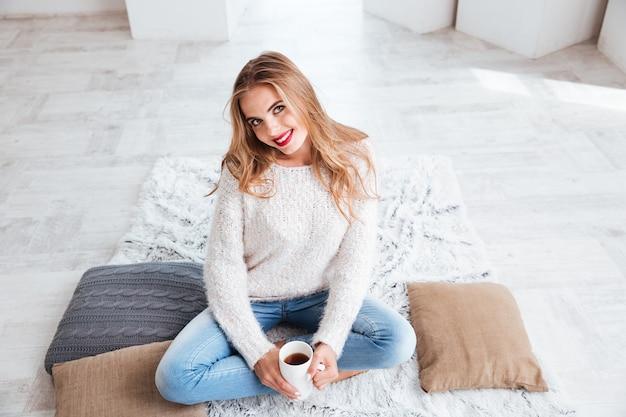 Feche o retrato de uma garota feliz e sorridente com um suéter, segurando uma xícara de chá e olhando para a frente dentro de casa
