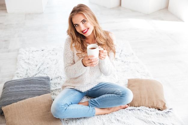 Feche o retrato de uma garota feliz sorridente com suéter segurando uma xícara de chá dentro de casa