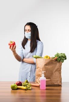 Feche o retrato de uma garota indiana bonita e feliz segurando uma sacola com legumes e frutas isoladas sobre uma parede branca