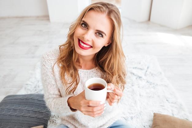 Feche o retrato de uma garota sorridente e atraente segurando uma xícara de chá e olhando para a frente dentro de casa