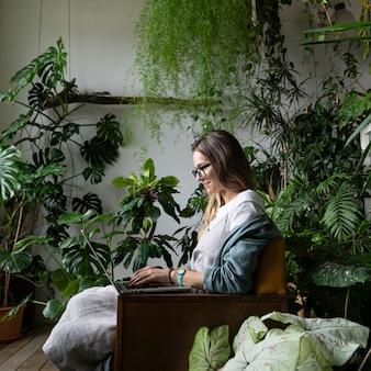 Feche o retrato de uma jardineira sorridente de óculos usar vestido de linho, sentado na cadeira em uma estufa, usando o laptop e falando na web call rodeado por plantas exóticas. jardinagem doméstica, freelance