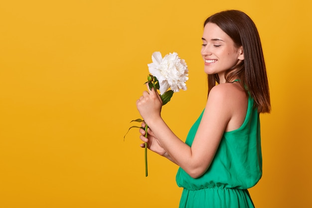 Feche o retrato de uma jovem adorável em pé isolado sobre rosa