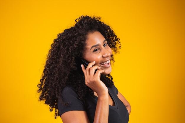 Feche o retrato de uma jovem afro-americana feliz falando com o celular em fundo amarelo.