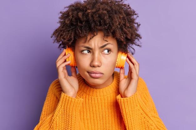 Feche o retrato de uma jovem afro-americana séria ouvindo uma trilha de áudio concentrada em algum lugar usando poses de fones de ouvido sem fio