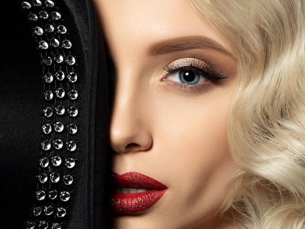 Feche o retrato de uma jovem bonita escondendo o rosto atrás de um chapéu preto