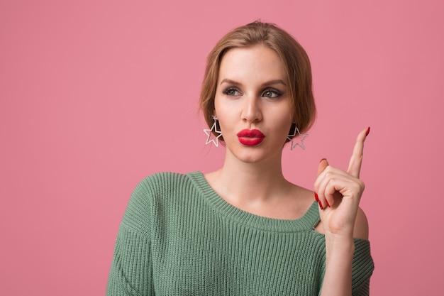 Feche o retrato de uma jovem bonita isolada em um fundo rosa, pensando, tendo uma ideia, segurando o dedo, estilo elegante, lábios vermelhos, tendência da moda de primavera, expressão de carinha engraçada