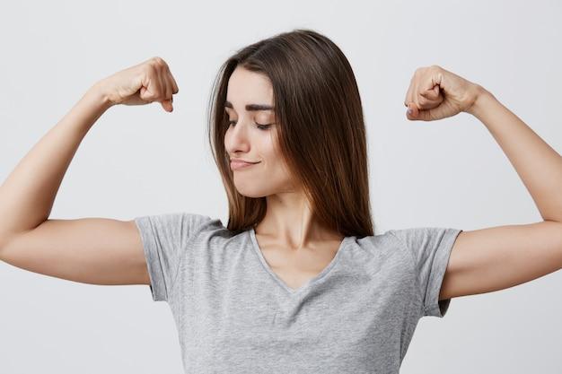 Feche o retrato de uma jovem bonita morena caucasiana engraçada bonita cabelos longos em t-shirt, brincando com os músculos, olhando para eles com expressão do rosto confiante e poderoso.
