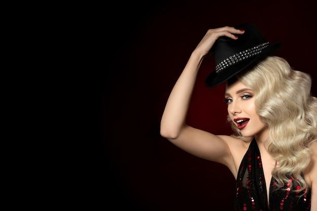 Feche o retrato de uma jovem bonita segurando o chapéu preto. bela maquiagem de noite - olhos dourados esfumados e lábios vermelhos com brilhos. conceito de show musical ou clube noturno.