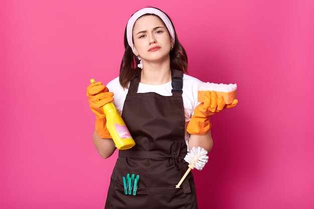 Feche o retrato de uma jovem caucasiana exuasted em camiseta casual branca, avental marrom e faixa de cabelo, possui esponja e detergente de limpeza, isolado sobre a parede rosa studio, pronto para fazer tarefas domésticas