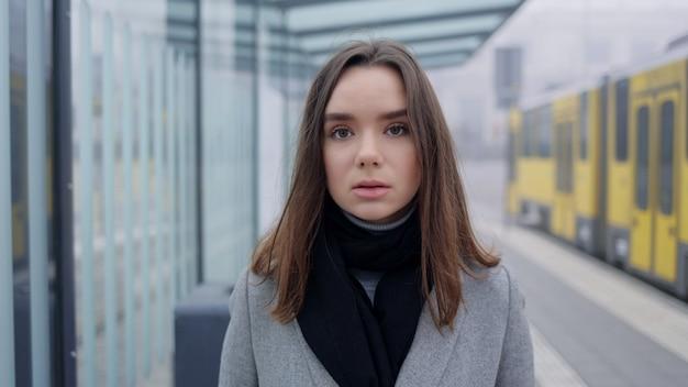 Feche o retrato de uma jovem com cabelo escuro na rua da cidade, esperando o bonde na parada