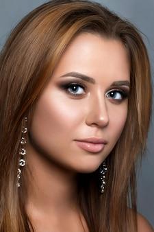 Feche o retrato de uma jovem com olhos esfumados bronze usando brincos longos. maquilhagem de noiva moderna. sobrancelhas perfeitas.