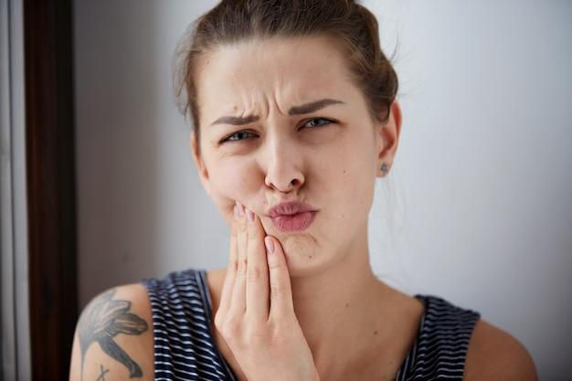 Feche o retrato de uma jovem com um problema sensível de dor de dente na coroa prestes a chorar