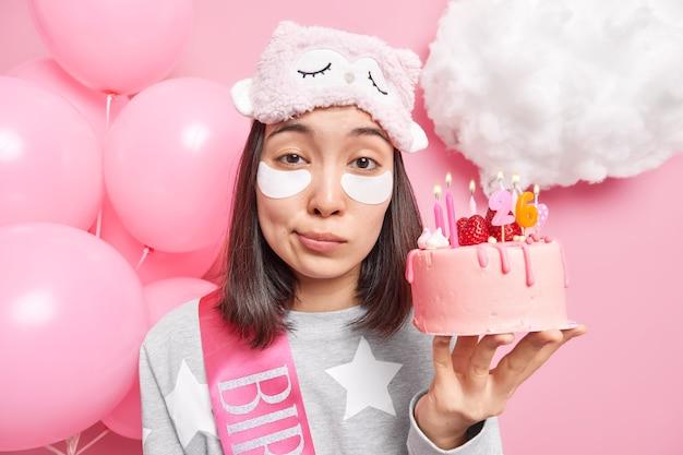 Feche o retrato de uma jovem e bonita modelo asiática aplicando manchas sob os olhos, usa máscara de dormir e pijama comemora aniversário