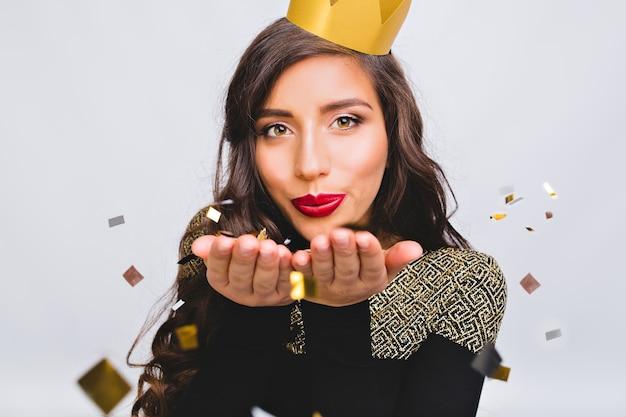 Feche o retrato de uma jovem elegante comemorando o ano novo, usando um vestido preto e uma coroa amarela, feliz festa de discoteca de carnaval, confetes cintilantes