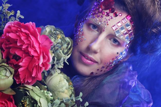 Feche o retrato de uma jovem em uma imagem criativa com flores grandes
