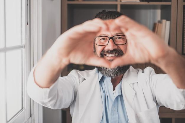 Feche o retrato de uma jovem enfermeira do sexo masculino caucasiano sorridente ou gp em uniforme médico branco mostra coração gesto de amor com a mão. médico de homem feliz mostra apoio e cuidado aos pacientes ou cliente no hospital.