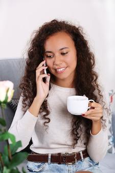 Feche o retrato de uma jovem falando ao celular com uma xícara de café na sala