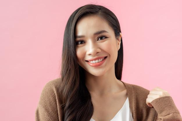 Feche o retrato de uma jovem feliz em fundo rosa