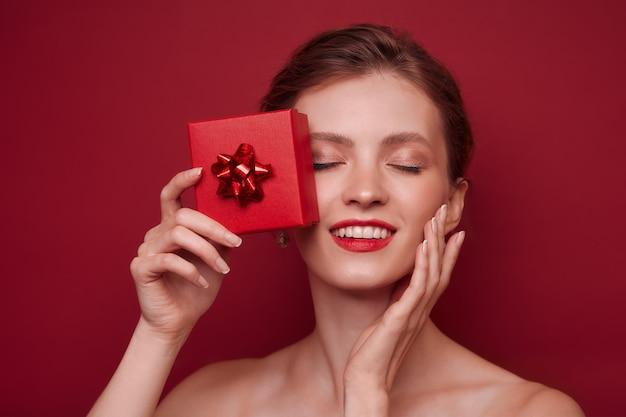 Feche o retrato de uma jovem feliz segurando um presente