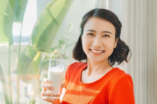 Feche o retrato de uma jovem grávida asiática segurando um copo de leite
