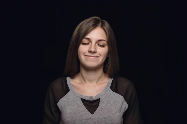 Feche o retrato de uma jovem isolada. modelo feminino com os olhos fechados. pensando e sorrindo. expressão facial, conceito de emoções humanas.