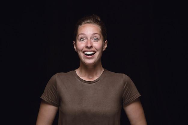 Feche o retrato de uma jovem isolada no fundo preto do estúdio. photoshot de emoções reais de modelo feminino. imaginando, excitante e surpreso. expressão facial, conceito de emoções humanas.