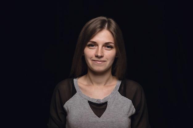 Feche o retrato de uma jovem isolada no fundo preto do estúdio. photoshot de emoções reais de modelo feminino. sorrindo, me sentindo feliz. expressão facial, conceito de emoções humanas puras e claras.