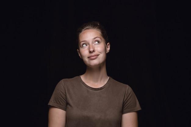 Feche o retrato de uma jovem isolada no fundo preto do estúdio.