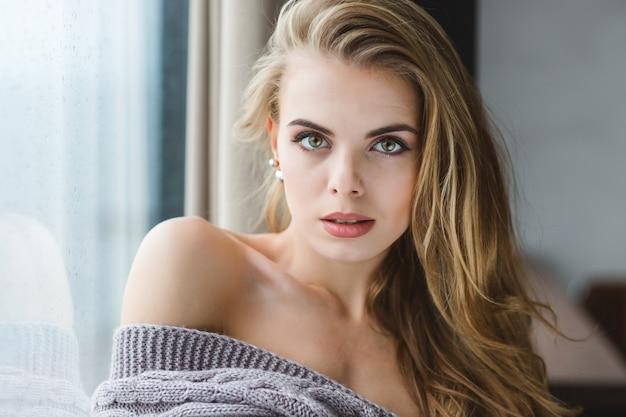 Feche o retrato de uma jovem loira atraente e sedutora