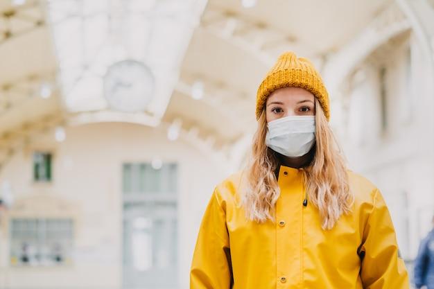 Feche o retrato de uma jovem loira com máscara protetora médica, casaco amarelo e gorro de malha paralisado de medo pelas notícias sobre o vírus cover-19. conceito de pandemia de coronavírus.