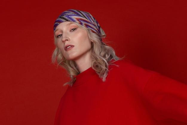 Feche o retrato de uma jovem loira com um lenço na cabeça sobre o fundo vermelho