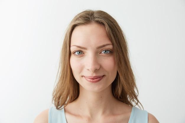 Feche o retrato de uma jovem menina loira bonita com olhos azuis sorrindo.