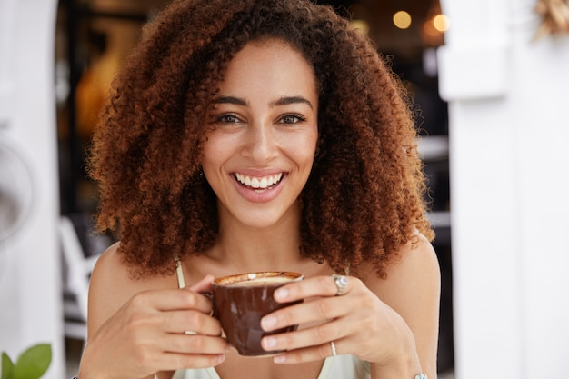 Feche o retrato de uma jovem modelo afro-americana com pele escura e saudável, dentes brancos, bebe café expresso aromático, passa o tempo de lazer em uma cafeteria