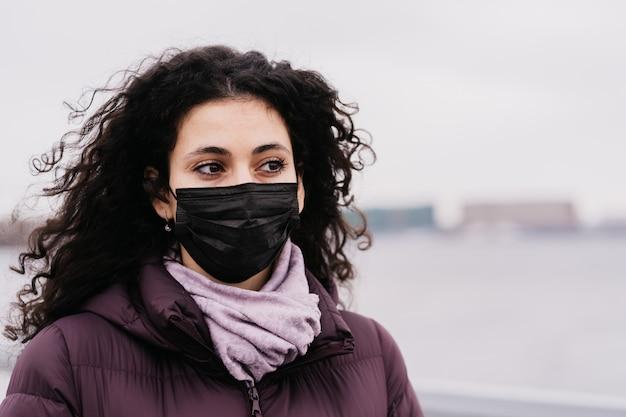 Feche o retrato de uma jovem morena com grandes olhos castanhos com a máscara de medicamento no rosto, pensando em vírus.