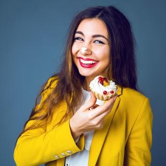 Feche o retrato de uma jovem morena com maquiagem brilhante, comendo bolo saboroso com frutas e creme.