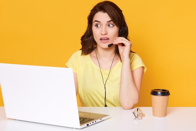 Feche o retrato de uma jovem morena feminina sentada na frente do computador portátil, mulher com fone de ouvido e microfone trabalhando como gerente na loja da internet