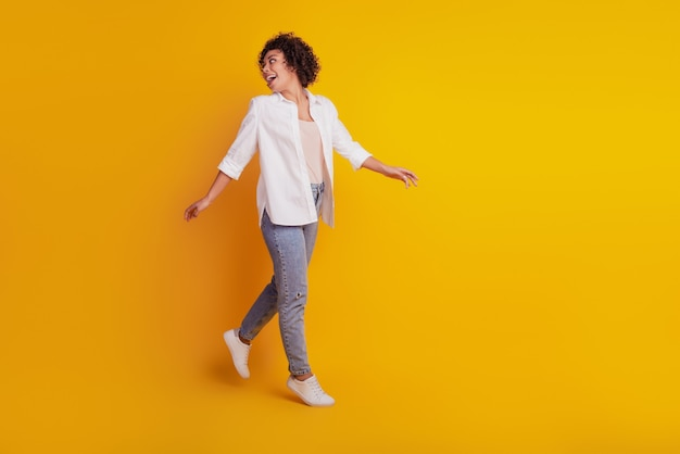 Feche o retrato de uma jovem mulher afro-americana atraente caminhada, olhe para trás na parede amarela