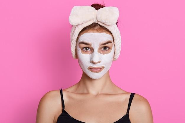Feche o retrato de uma jovem mulher aplica máscara facial de argila, tem uma faixa branca na cabeça, parece sério, posando contra um fundo rosa, olha para a câmera.