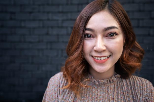 Feche o retrato de uma jovem mulher asiática sorrindo