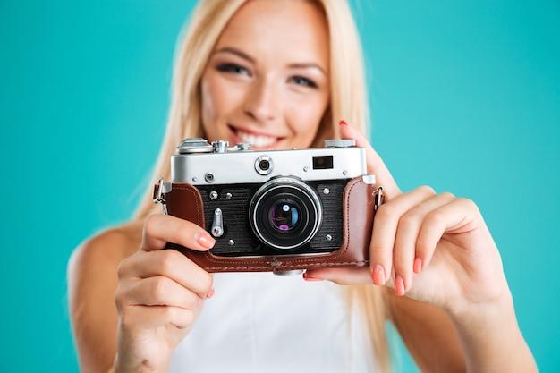 Feche o retrato de uma jovem mulher atraente com uma câmera retro isolada no fundo azul