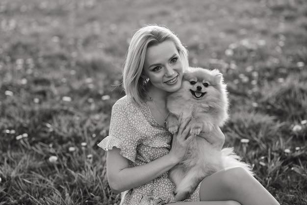 Feche o retrato de uma jovem mulher atraente sorridente, abraçando o spitz da pomerânia.