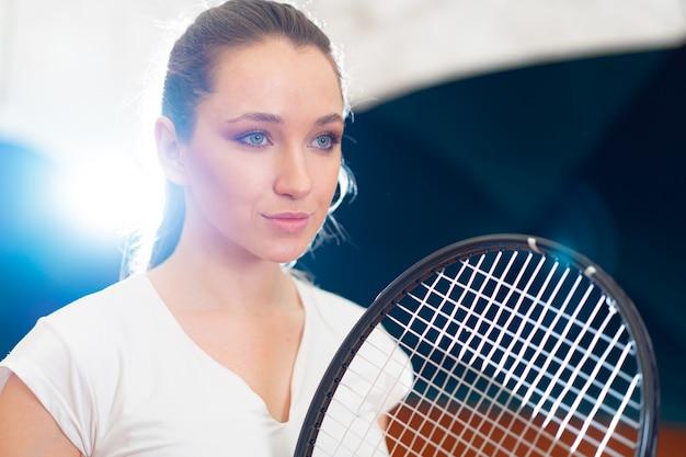 Feche o retrato de uma jovem mulher atraente tenista segurando a raquete de tênis