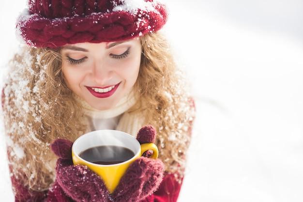 Feche o retrato de uma jovem mulher bonita com uma xícara de café quente